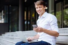 Zakenman die mobiele telefoon en laptop in openlucht met behulp van royalty-vrije stock afbeeldingen