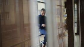 Zakenman die mobiele telefoon houden terwijl status bij de bureaubouw venster stock video