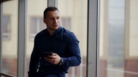 Zakenman die mobiele telefoon houden terwijl status bij de bureaubouw venster stock videobeelden