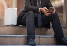 Zakenman die mobiele telefoon in stad met behulp van stock afbeelding