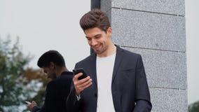 Zakenman die mobiele telefoon voor tekstoverseinen met behulp van Knappe mens die zaken app op smartphone gebruiken bij de bureau stock footage