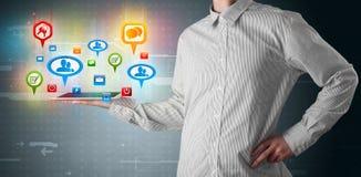 Zakenman die moderne tablet met kleurrijke sociale tekens voorstellen Stock Foto's