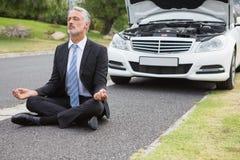Zakenman die na zijn opgesplitste auto mediteren Royalty-vrije Stock Foto