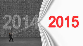 Zakenman die neer het gordijn die van 2015 trekken de oude baksteen van 2014 behandelen wa Royalty-vrije Stock Foto's