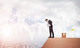 Zakenman die neer van dak en moderne cityscape achtergrond bekijken Gemengde media Stock Fotografie