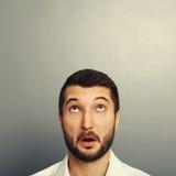 Zakenman die omhoog over grijs kijken Stock Fotografie