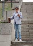 Zakenman die onderaan de treden loopt Directeur het texting op de stedelijke achtergrond Progressief bedrijfsconcept De ruimte va Royalty-vrije Stock Foto's
