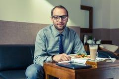 Zakenman die ontbijt thuis/hotel eten Binnenfoto Stock Foto's
