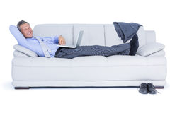 Zakenman die op bank liggen die zijn laptop met behulp van die bij camera glimlachen Royalty-vrije Stock Afbeeldingen
