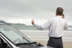 Zakenman die op celtelefoon spreekt naast zijn auto stock foto