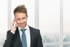 Zakenman die op celtelefoon tegen venster spreken Stock Fotografie