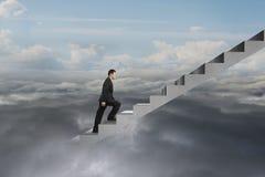Zakenman die op concrete treden met natuurlijke bewolkte hemel beklimmen Stock Foto's