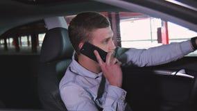 Zakenman die op de telefoon in de auto spreken stock footage