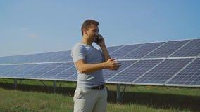 Zakenman die op de telefoon op het gebied met zonnepanelen spreken stock videobeelden