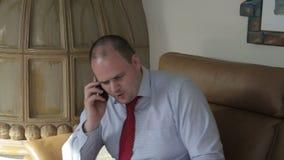 Zakenman die op de telefoon in zijn verstoorde woonkamer en blikken spreken stock footage