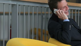 Zakenman die op de telefoonzitting spreken op een zakenreis stock videobeelden