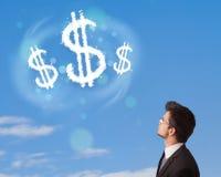 Zakenman die op de wolken van het dollarteken op blauwe hemel richten Stock Afbeeldingen