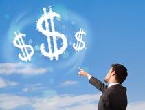 Zakenman die op de wolken van het dollarteken op blauwe hemel richten Stock Foto