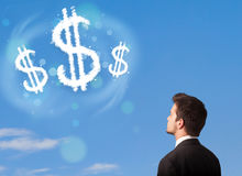Zakenman die op de wolken van het dollarteken op blauwe hemel richten Royalty-vrije Stock Afbeeldingen