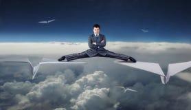 Zakenman die op document vliegtuigen vliegen Stock Foto's