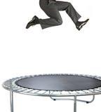 Zakenman die op een trampoline op wit stuitert Stock Foto's
