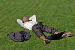 Zakenman die op gras ligt Stock Fotografie