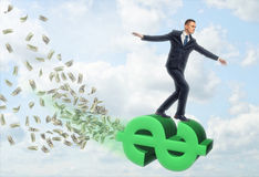 Zakenman die op groot dollarteken vliegen Stock Afbeeldingen