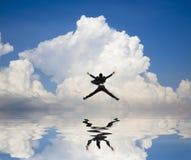 Zakenman die op het water en de wolk springt Stock Afbeeldingen