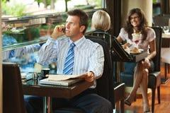 Zakenman die op mobiel in koffie spreekt Royalty-vrije Stock Foto's