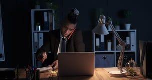 Zakenman die op mobiele telefoon spreken en nota's nemen op nachtkantoor stock video
