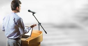 Zakenman die op podium op conferentie met heldere achtergrond spreken Stock Afbeelding