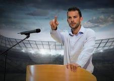 Zakenman die op podium op conferentie met sportenstadion spreken Stock Foto's
