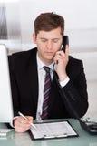 Zakenman die op telefoon in bureau spreekt Royalty-vrije Stock Afbeelding