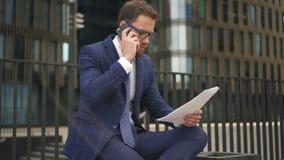 Zakenman die op telefoon spreken, die documenten houden zittend op achtergrond van de bureaubouw stock videobeelden