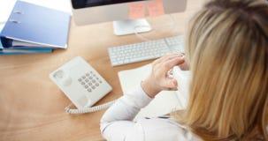 Zakenman die op telefoon spreken en aan computer werken stock footage