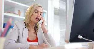 Zakenman die op telefoon spreken en aan computer werken stock videobeelden