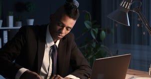 Zakenman die op zelfklevende nota schrijven en het plakken op laptop op nachtkantoor stock videobeelden
