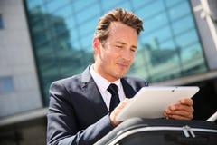Zakenman die in openlucht tablet gebruiken stock foto