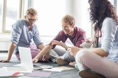 Zakenman die plan op laptop verklaren aan collega's op creatief kantoor Stock Afbeeldingen