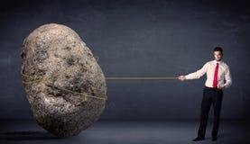 Zakenman die reusachtige rots met een kabel trekken stock foto's