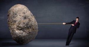 Zakenman die reusachtige rots met een kabel trekken stock afbeeldingen