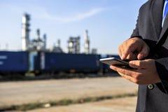 Zakenman die rond de installatie van de olieraffinaderij met duidelijke hemel controleren royalty-vrije stock afbeelding