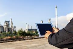 Zakenman die rond de installatie van de olieraffinaderij met duidelijke hemel controleren royalty-vrije stock foto