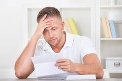 Zakenman die in schok aan een brief reageren Stock Foto
