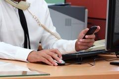 Zakenman die slimme telefoon met behulp van tijdens het werken Stock Foto's