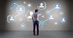 Zakenman die sociale netwerkinterface op een muur 3D renderin gebruiken Stock Afbeelding