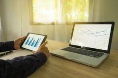 Zakenman die tablet gebruiken aan de situatie op de marktwaarde, stock fotografie