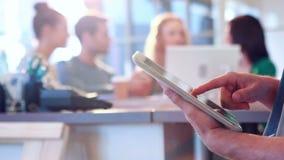 Zakenman die tabletcomputer met zijn collega's achter hem met behulp van stock videobeelden
