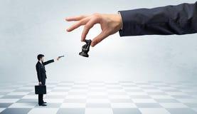 Zakenman die tegen groot schaakstuk op een grote hand vechten stock foto