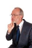 Zakenman die teken met vinger over mond geven Stock Afbeeldingen